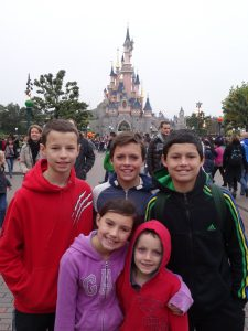FIve children in front of the Disney castle