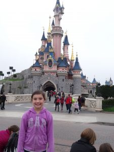 a girl stands in front of a Disney castle