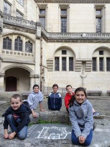 Five children sit in a chateau courtyard