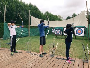 Three children poised with bows and arrows as they prepare to hit targets at Adventure Pursuits on Berny Riviere, fun-filled parc in Northern France