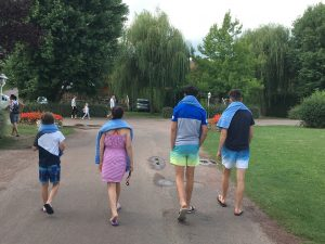 Four children walk off with towels around their shoulders towards the amazing pool complex at Berny Riviere