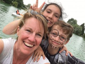 A mother and two children smile at the camera for a selfie in front of lake with a pedalo on