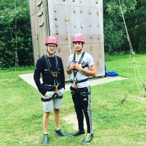 Two teenage boys in harnesses and hard hats stand in front of a climbing wall at Eurocamp's family-friendly Berny Riviere parc in northern France
