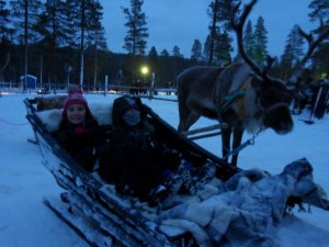 A boy and girl sit in a sleigh next to a reindeer