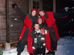 A young brother and sister pose with two elves in the snow in Lapland