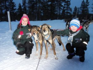 A young boy and girl stroke husky dogs in the snow in Lapland